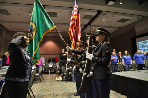 Photo of a female military personnel sitting at a desk with a laptop and an american flag behind her