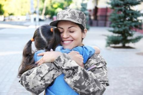 Female service member hugging a small child