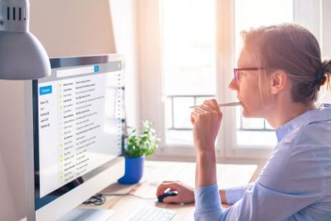 Woman sitting in front of a computer screen with email on the screen